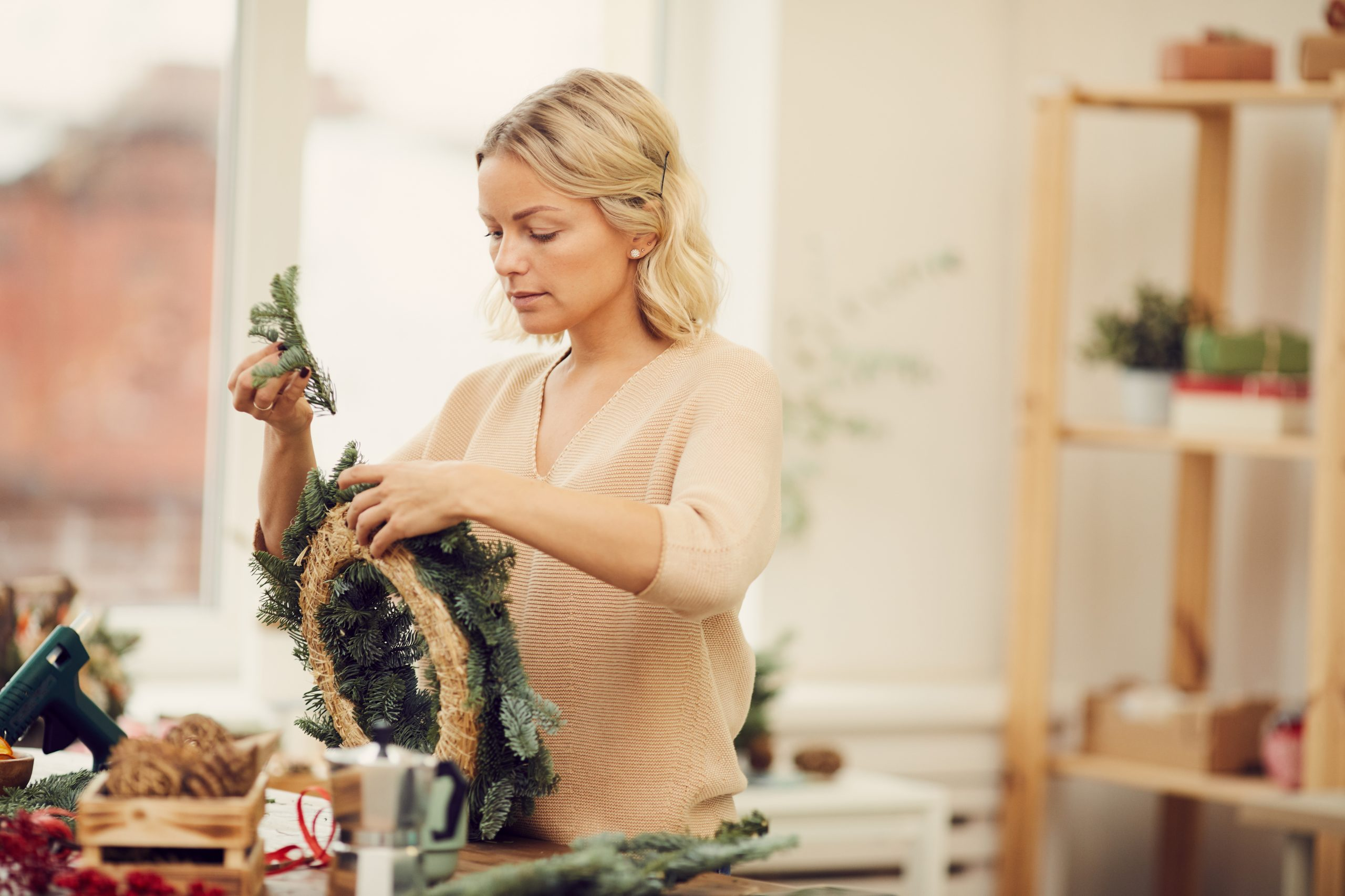 Serious busy beautiful young woman in casual sweater standing at table in workshop and attaching coniferous branches in wreath while preparing decorations for Christmas