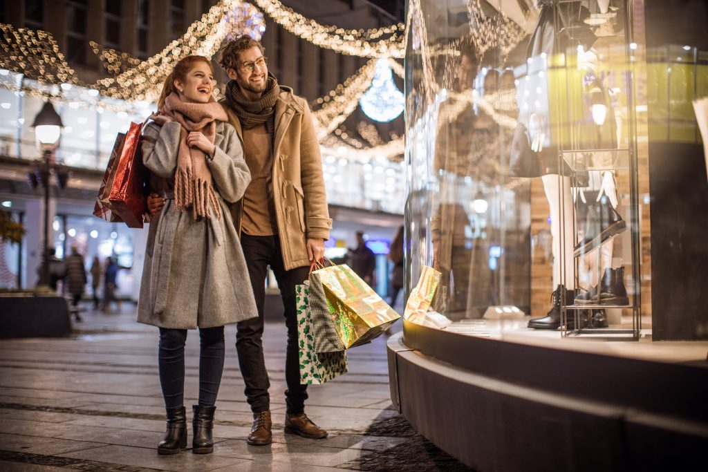 Young couple walking in shopping mall for Christmas. Holding Christmas gifts and wearing warm clothing.